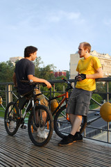 two young men in sport clothes standing on bridge near bicycles