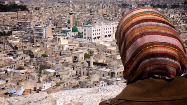 Woman wearing headscarf looking out over Aleppo