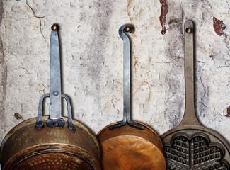 Küchenwand mit alten Pfannen