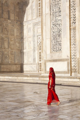 Woman in red sari/saree walking past Taj Mahal.