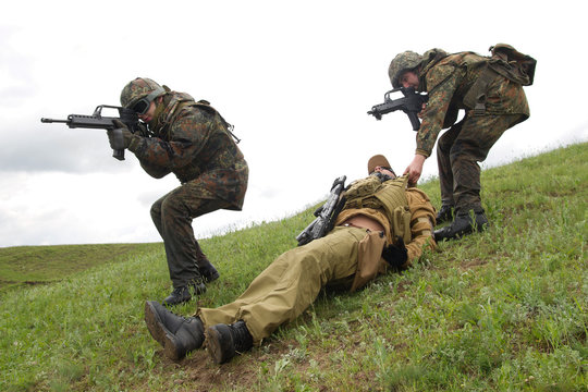 Soldiers saving their wounded colleague.Armed military men with guns draging dead soldier from battlefield.Soldier shot dead on battle fied at war.Camouflage and automatic guns