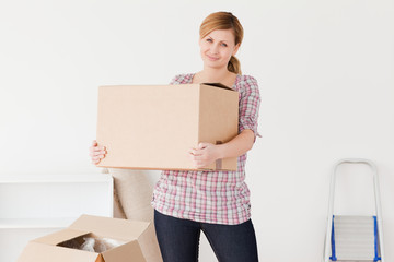 Blond-haired woman carrying cardboard boxes