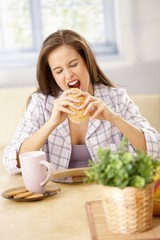 Hungry woman biting into sandwich