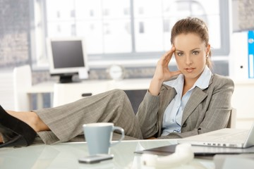 Young businesswoman sitting tired in office
