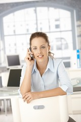 Young female using mobile sitting in office