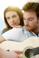 Romantic couple sitting playing guitar outdoor ó