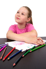 The girl draws a picture color pencils