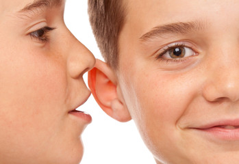 Zwei Jungen flüstern sich Neuigkeiten ins Ohr