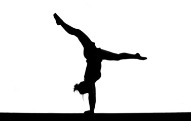 Wall Mural - silhouette of female gymnast doing handstand on balance beam