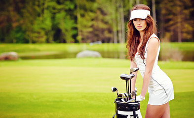 Portrait of an elegant woman playing golf on a green