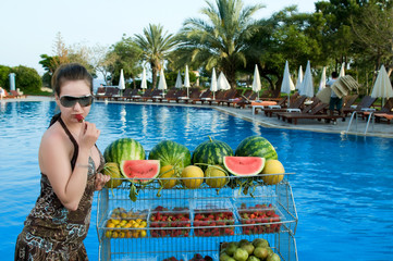 Young girl eating strawberry in front of a swimming pool.