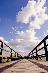 wooden bridge perspective with clouds