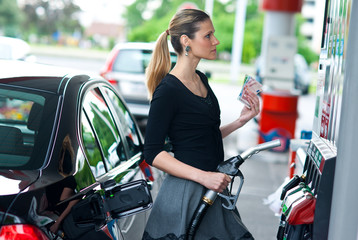 woman holding money on gas station