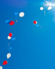 Colorful balloons, flying toward the sun against the blue sky