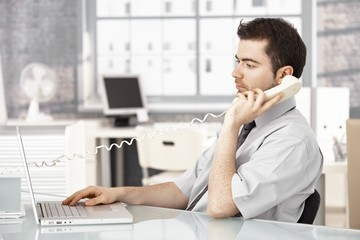 Young male working in office talking on phone