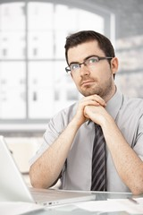 Portrait of young male sitting at desk thinking
