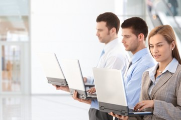 Young professionals using laptop in office lobby
