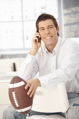 Happy businessman on phone, holding football