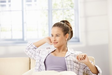 Attractive woman stretching on sofa
