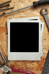 Old photo frames on wood background with a working tool