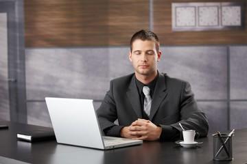 Top manager meditating in elegant office