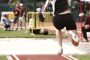 """Female athlete competing on the """"long jump"""" event"""