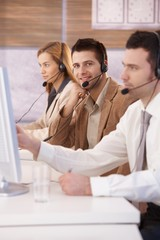 Happy dispatcher working in call center smiling