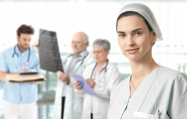 Mid-adult nurse with medical team in background