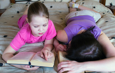 Mother and daughter reading in bed book