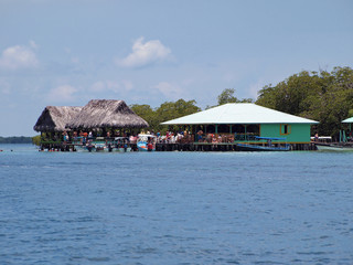 Over the water tropical bar restaurant with tourist and boat, Coral cay, Bocas del Toro, Panama, Central America