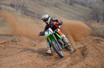 Fototapete - Motocross rider with a strong slope turns sharply