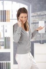Cheerful woman on phone call at home
