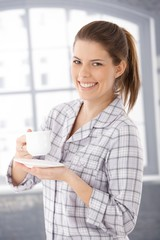 Happy woman in pyjama with coffee cup