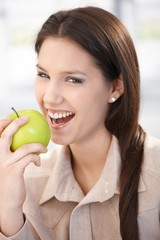 Happy woman biting an apple smiling