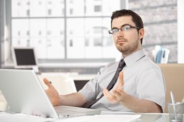 Young stock broker using laptop gesturing
