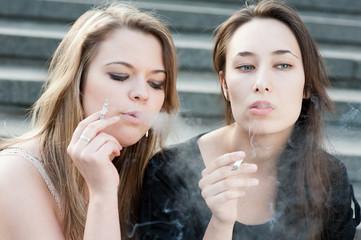 Two sad young girls smoke