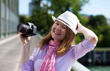 blond woman holding cowboy's hat and camera