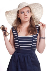 A girl in a straw hat with sunglasses in hand