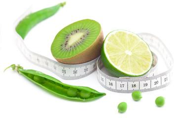 lime,peas,kiwi and measure tape isolated on white