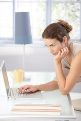 Young woman browsing internet at home