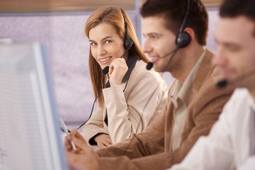 Pretty female dispatcher in call center smiling