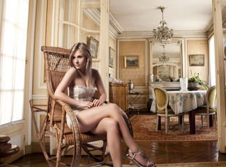 blond girl sitting in a rocking chair near the window