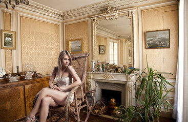 blond girl sitting in a rocking chair near the fireplace