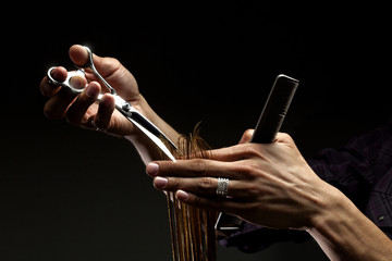 A close-up of hairdresser's hands cutting hair