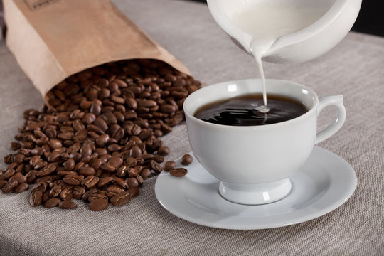Milk pouring into a cup of coffee