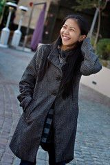 Pretty Woman Laughing and Smiling with a Long Coat Outdoors