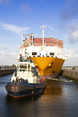 Container ship with tug boat in lock