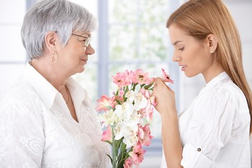Senior mother and daughter with flowers