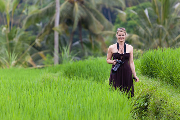 Smiling Woman with Camera in Bali Rice Field