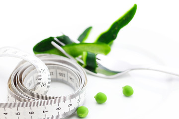 peas,fork ,cucumber skin and measure tape on a plate isolated on